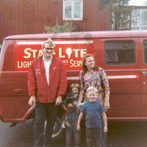 Jim, Joanne, Scott, and Chris holding Heidi in front of the first service truck.